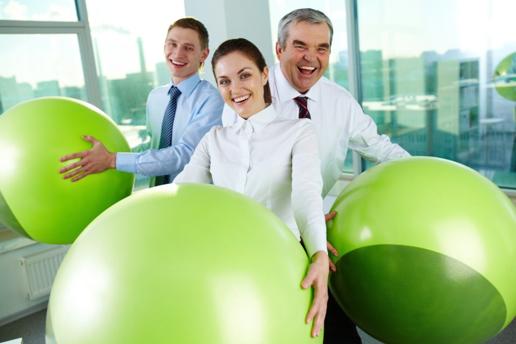 Portrait of joyful business partners with big balls looking at camera in office