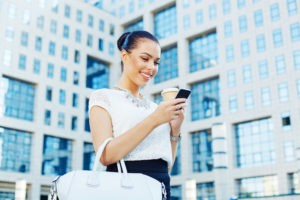 Young businesswoman holding coffee to go and texting massage