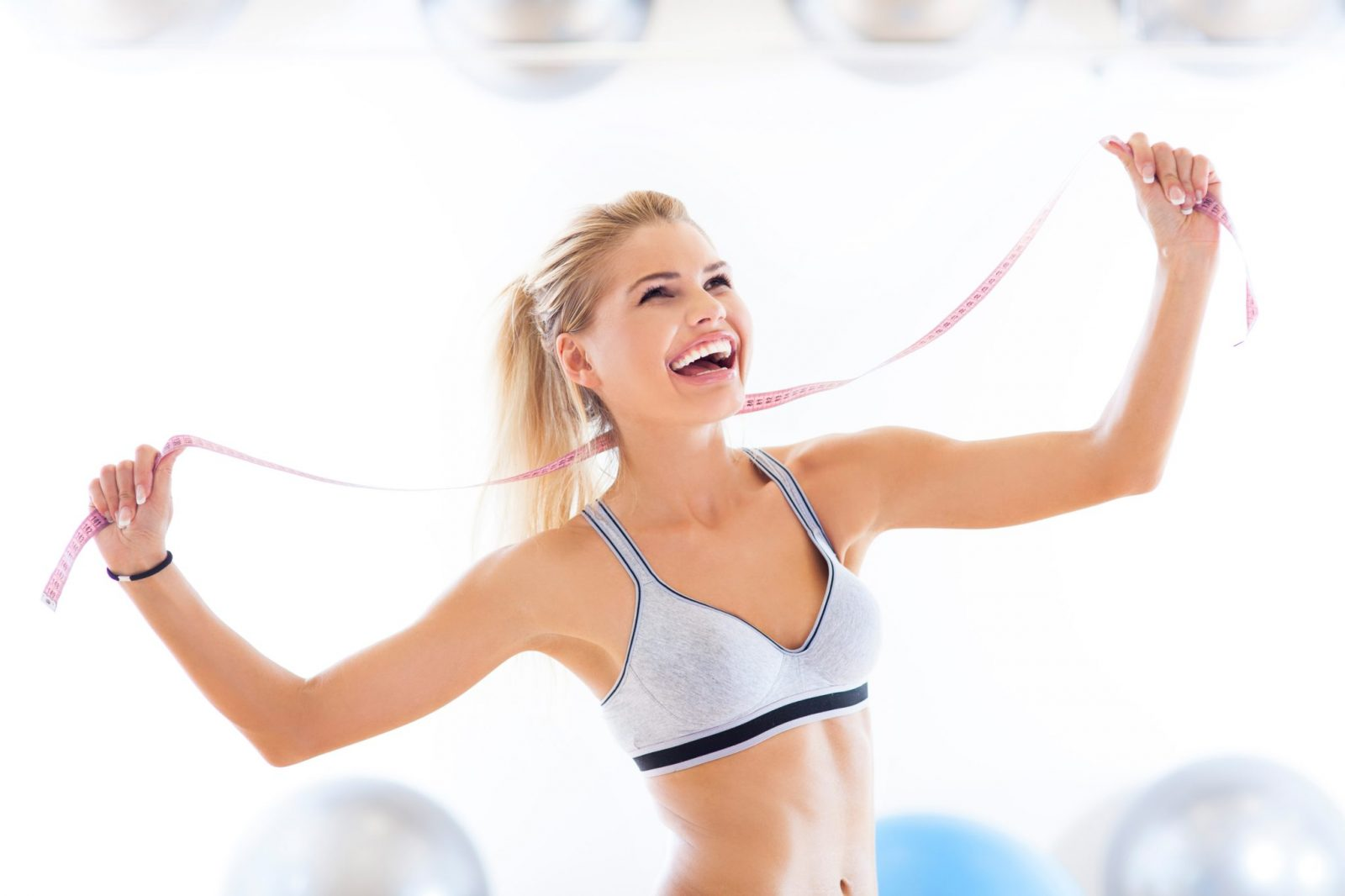 happy woman who lost weight holding a tape measure with exercise balls in the background